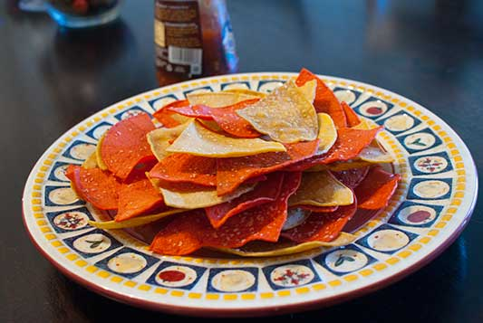 Baked tortilla chips are a simple and delicious snack that can be made in just minutes. Enjoy them hot with your favorite salsa.