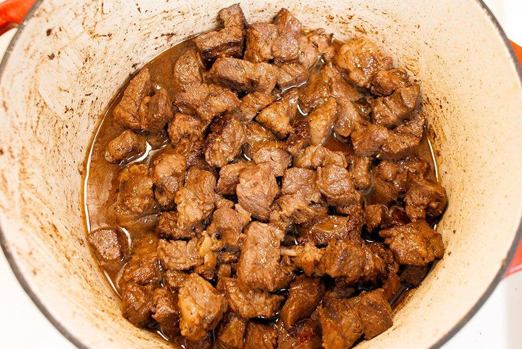 Add all the beef and juices back to the pan and pour in beef stock