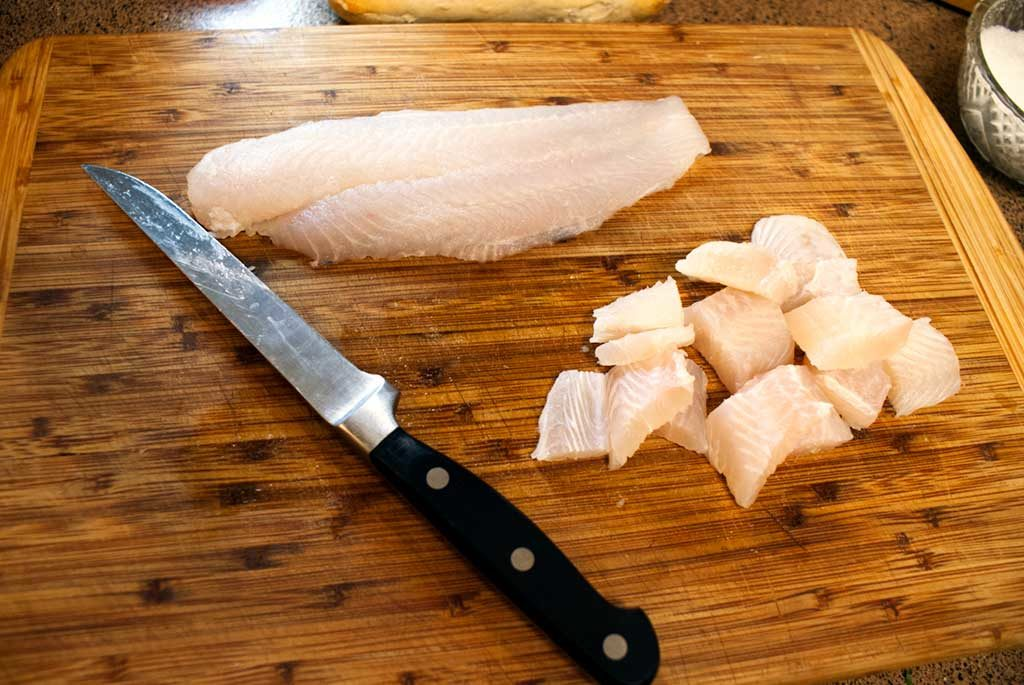 Cut whitefish (In this case, it's swai fillets) into cubes, if desired. Or you could just poach the fillets whole.
