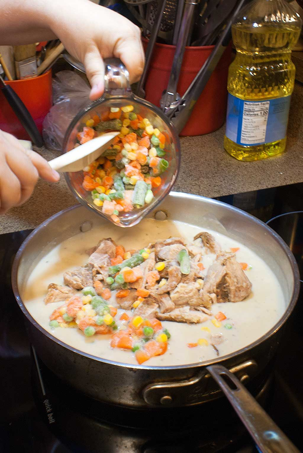 Adding leftover turkey and frozen mixed vegetables to soup mixture