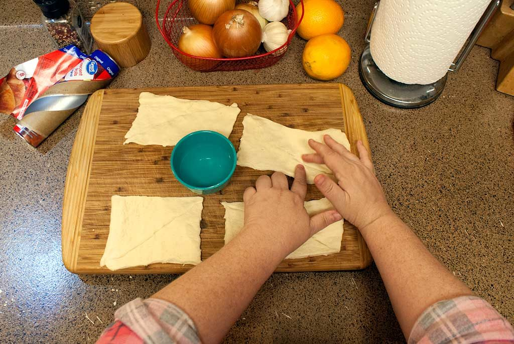 Sealing tears in crescent dough with wet finger