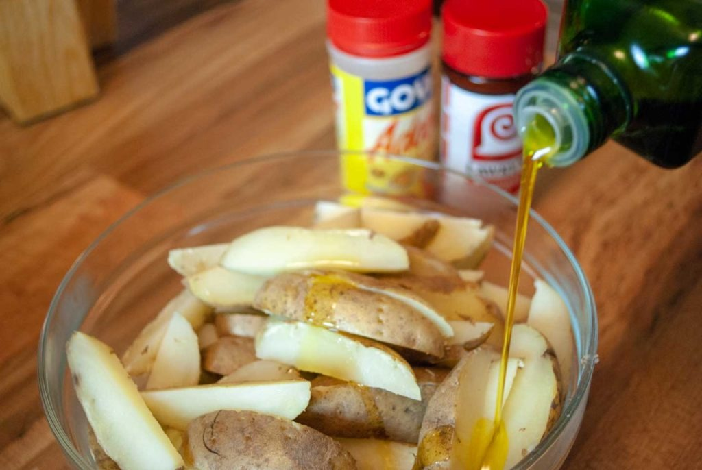 Pouring olive oil over potato wedges