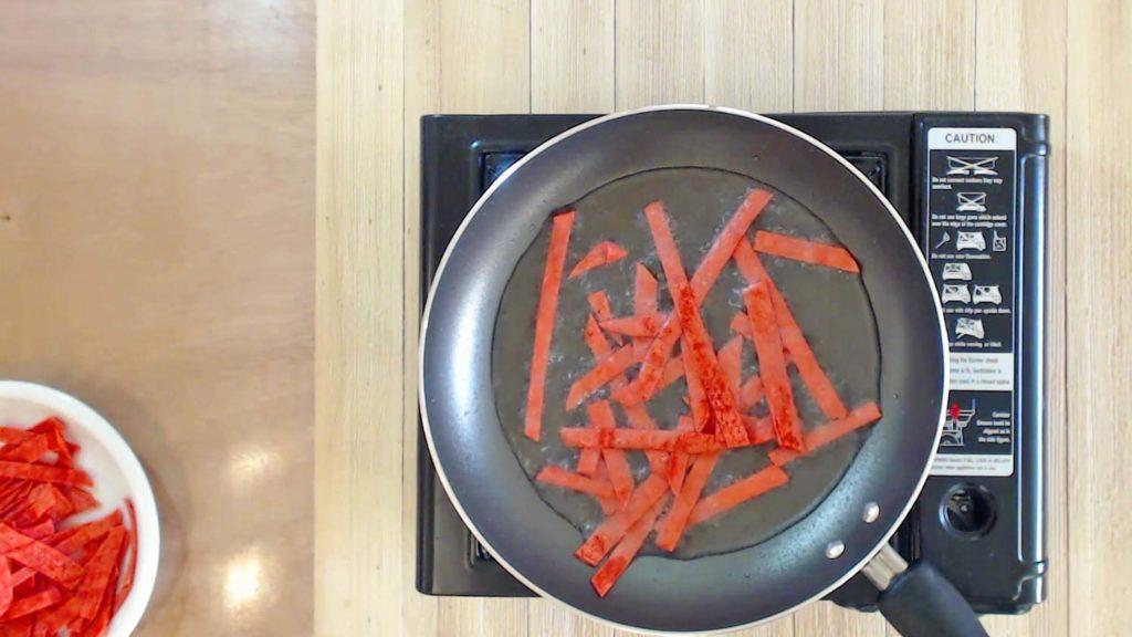 Frying tortilla strips in hot oil.