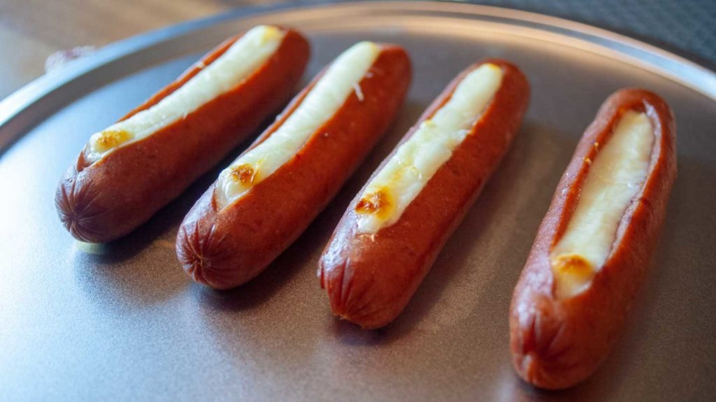 Cooked sausages stuffed with melted and browned string cheese