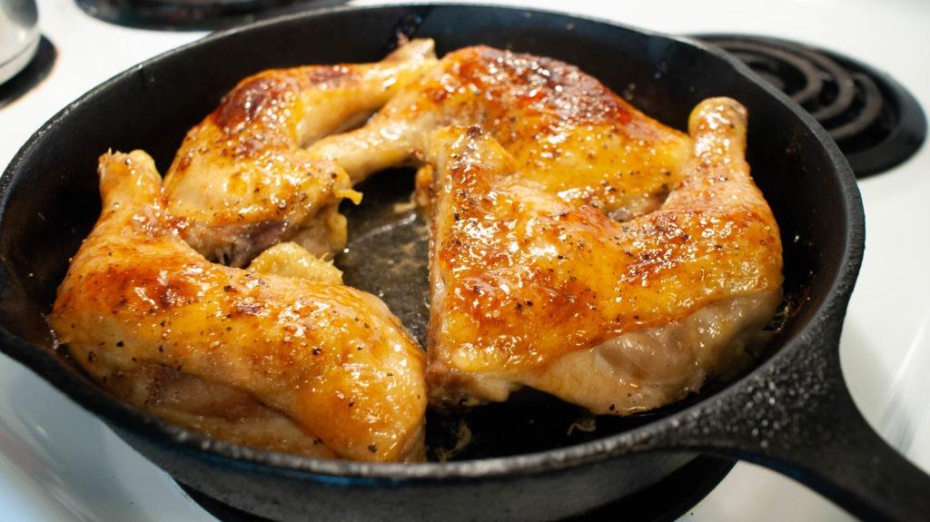 plum glazed chicken leg quarters in a cast iron skillet