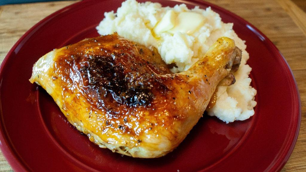 Plum glazed chicken leg quarters plated with lemon garlic mashed potatoes