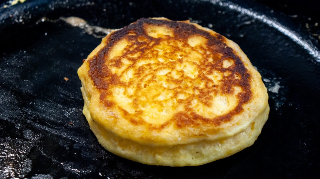 Hoecake cooking in a cast iron skillet