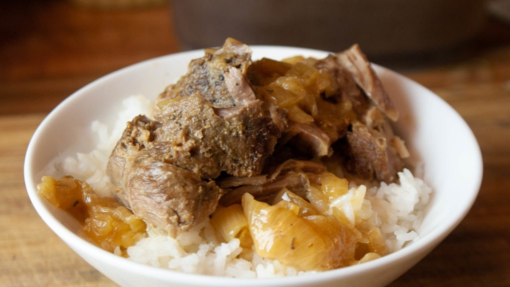 Beer and onion braised pork roast over white rice in a bowl