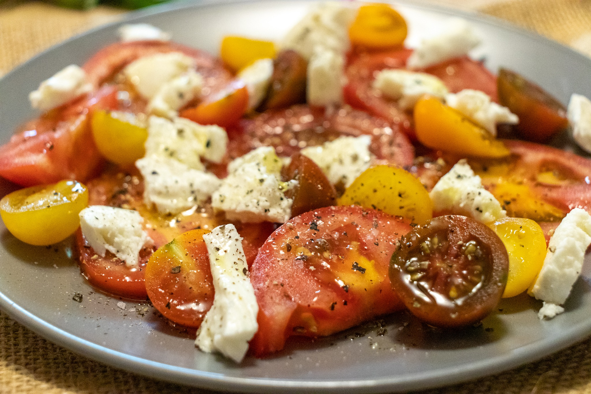 Seasoned tomatoes and cheese on a plate.