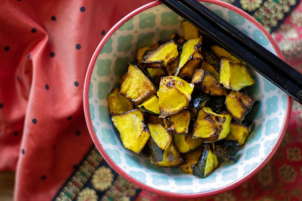 Roasted acorn squash with honey glaze in bowl with chopsticks