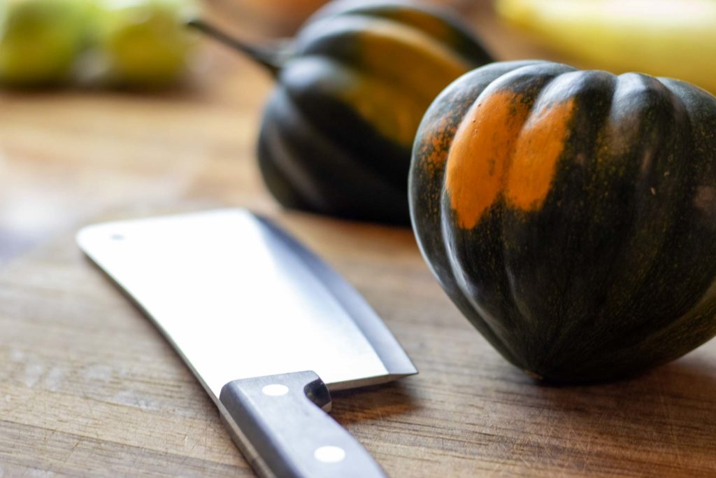 Acorn squash on counter with cleaver