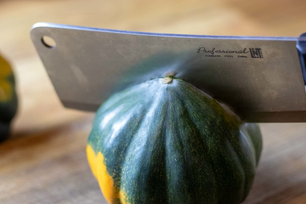 Cleaver cutting acorn squash in half