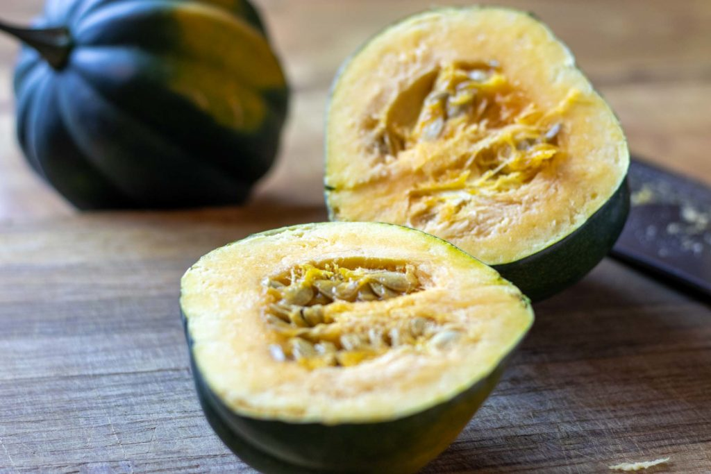 Halved acorn squash on counter in sunlight