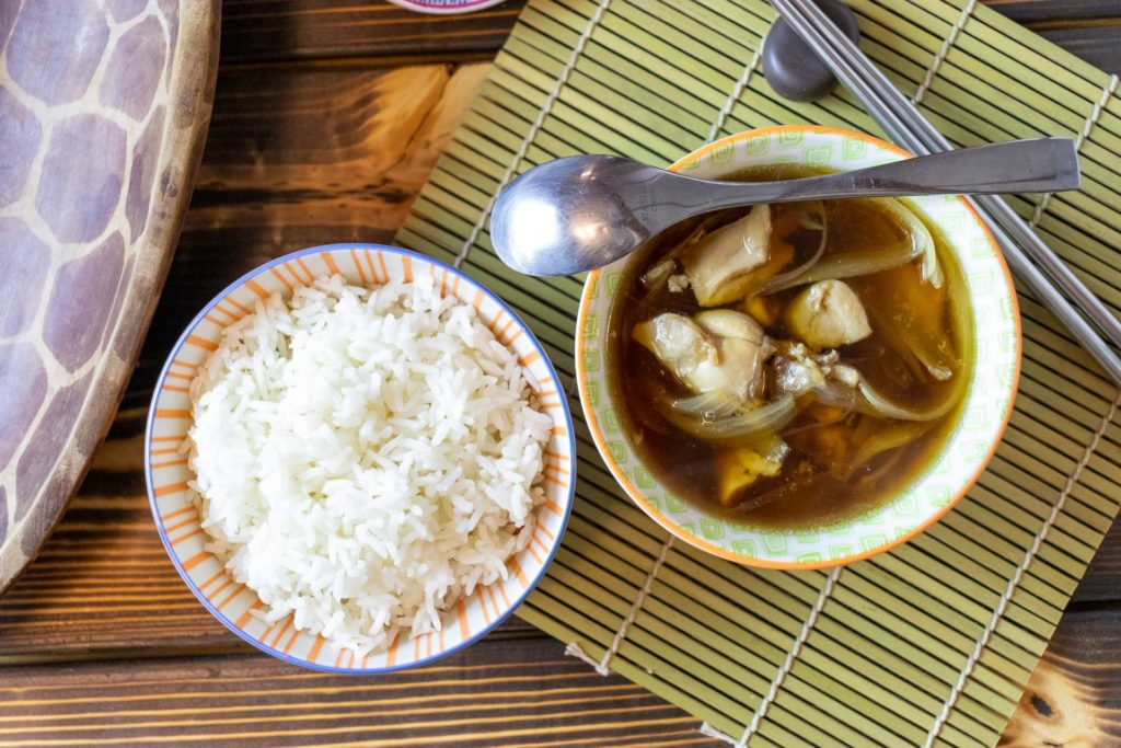 Asian-inspired chicken soup alongside a bowl of rice.