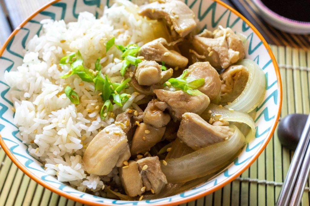 Simmered chicken and onions on top of rice with green onions