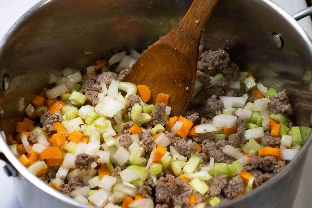 Sausage celery carrots and onion in a pot