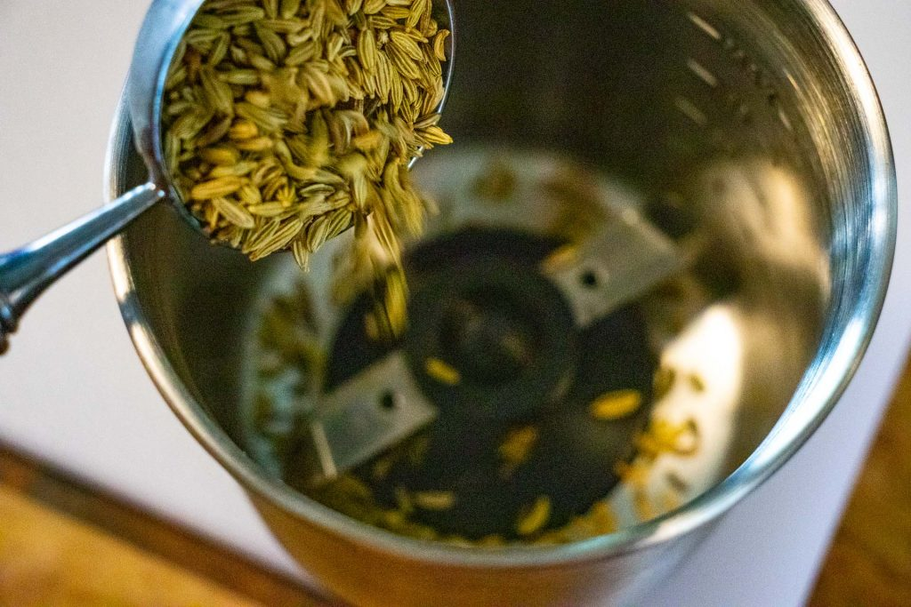 Fennel seeds pouring into a spice grinder